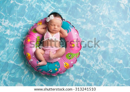 Nine day old newborn baby girl sleeping on a tiny inflatable swim ring. She is wearing a crocheted pink and white bikini. - stock photo