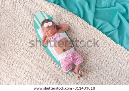 Nine day old newborn baby girl sleeping on a tiny surfboard. She is wearing pink and white crocheted boardshorts, bikini top and sandals. - stock photo