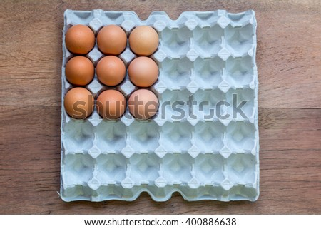 Nine Eggs in paper tray on wooden background. - stock photo