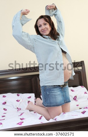 Nine month pregnant beautiful woman in bad - stock photo