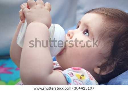 Nine months old baby drinking milk from bottle holding with both hands