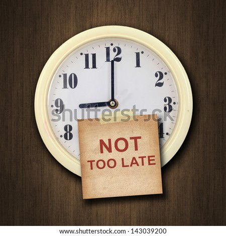 nine o'clock on the wall clock  with the old paper short note and text not too late on wood background - stock photo