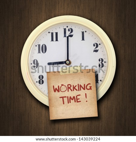 nine o'clock on the wall clock  with the old paper short note and text working time on wood background - stock photo