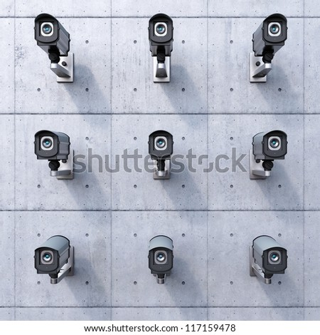 nine security cameras on a concrete wall - stock photo