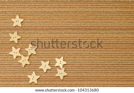 Nine star shaped buttons on a textured fabric with copy space