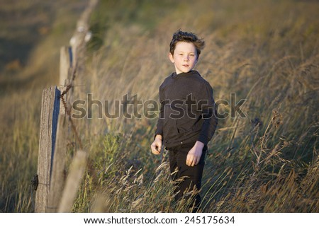 Nine year old boy standing in long grass near a farm fence in late afternoon sunlight - stock photo