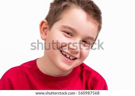 Nine years old boy looking at camera trustfully with his toothy smile. - stock photo
