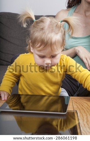 nineteen month aged blonde baby yellow shirt with pigtails looking at blank screen tablet on brown table - stock photo