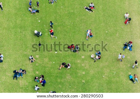 Ninety degrees view of people relaxing on a meadow.