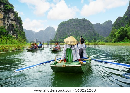 NINH BINH PROVINCE, VIETNAM - OCTOBER 14, 2015: Tourists traveling in boats along the Ngo Dong River at the Tam Coc portion. Rowers using their feet to propel oars. Landscape formed by karst towers. - stock photo