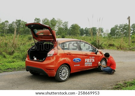 Ninh Binh, Viet Nam - April 16, 2014: Unidentified man cleaning his car (Ford Fiesta EcoBoost 1.0) on the road in Vietnam