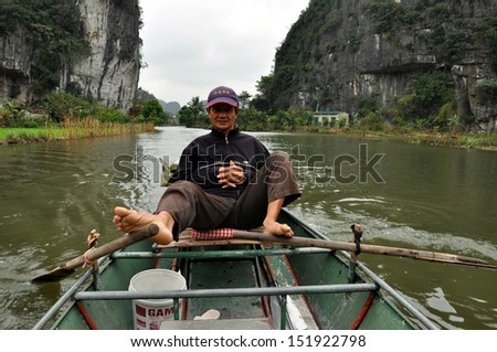 NINH BINH, VIETNAM - FEB 21: Unidentified travelers with rower guides in a boat trip visiting rice fields and limestone mountains along the Ngo Dong river at Tam Coc. On Feb 21, 2013 in Ninh Binh, Vietnam