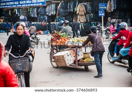 NINH BINH, VIETNAM - JANUARY 23, 2015: A woman in traditional conical hat sells vegetables and fruits in a movable vehicle. Exotic food is one of the main attraction for tourists in Vietnam.