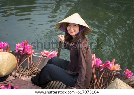 Ninh Binh, Vietnam - Oct 9, 2016: Portrait Vietnamese girl sits on boat wearing conical hat, in Yen stream