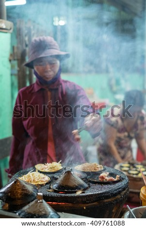 Ninh Thuan, Vietnam - April 16, 2016: Women is making Vietnamese Sizzling cake (pancake), named for the loud sizzling sound it makes when the rice batter is poured into the hot skillet