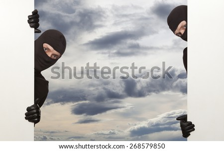 Ninja. Robber hiding behind a empty white sign with space for text - stock photo