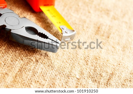 Nippers and a measuring roulette on a fabric. - stock photo