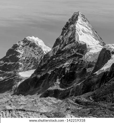 Nirekha (6169 m), Kangchung (6062 m) and Moon betwen them - Gokyo region, Nepal (black and white) - stock photo