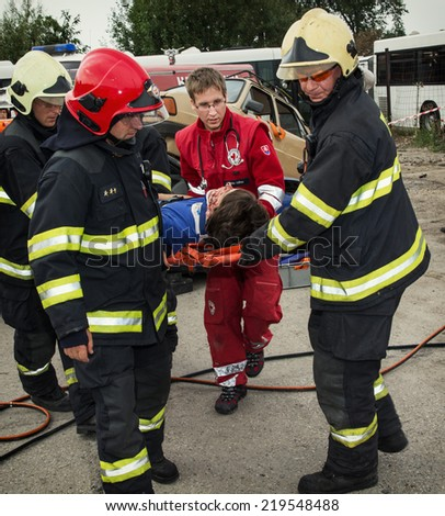 Nitra, Slovakia - September 06, 2014: Simulation of a car accident. Firefighters and rescuers taking away injured on a stretcher by the car accident. - stock photo