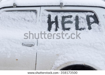 Niva car under a layer of snow and with a sign HELP on a snowy glass - stock photo