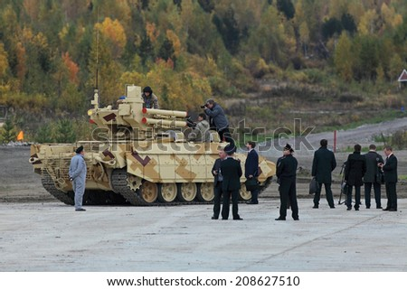 "NIZHNY TAGIL, RUSSIA - SEP 25, 2013: The international exhibition RUSSIA ARMS EXPO (RAE-2013). Customers visiting BMPT Ramka - Russian Tank Support Fighting Vehicle ""Terminator"""