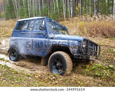 NIZHNY TAGIL. RUSSIA - SEPTEMBER 22, 2012: Russian Plain Road in the heart of Siberia. Wheel drive vehicle leaves the swamp