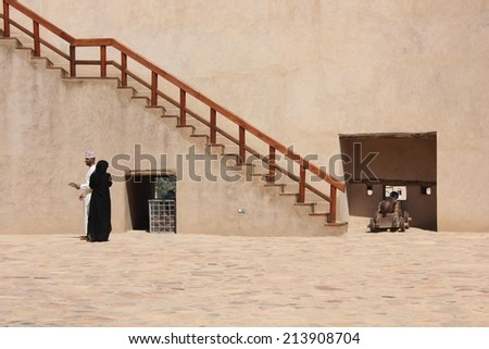Nizwa, Oman, October 21, 2013: an islamic couple walking inside the Nizwa Fort Castle, a massive castle in Nizwa and the Oman's most visited national monument. - stock photo