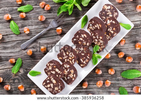 No Bake Hazelnuts Peanuts Chocolate Cookies on a square dish on an old rustic table with bunch of mint, view from above - stock photo