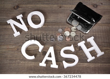 No Cash Sign Made From White Wood Letter And Empty Black Purse With Different British Coins On The Rough Wood Background, Top View, Conceptual Image - stock photo