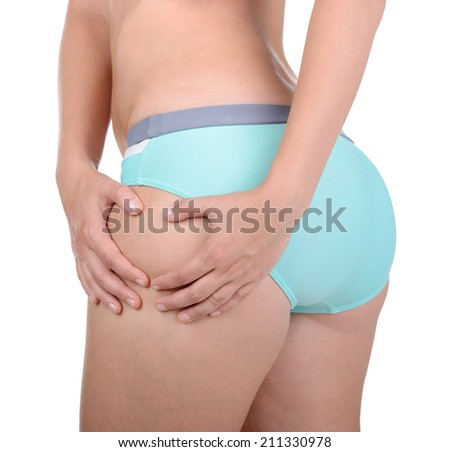 No cellulite. Close-up of woman in black panties touching her buttocks while isolated on white