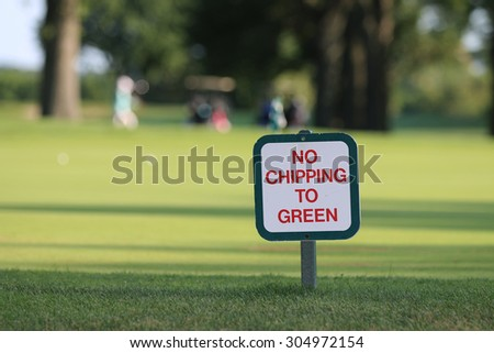 No Chipping to Green Golf Course Sign Positioned near Green, with A Golf Cart and Golfers in the Background. - stock photo