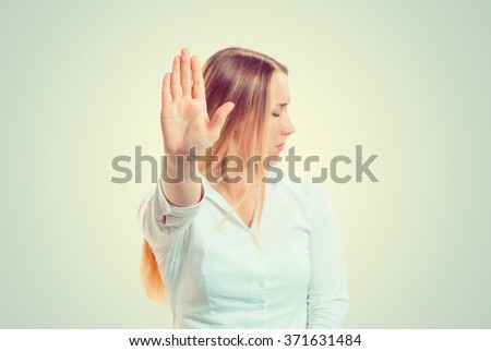 No Closeup portrait young angry serious woman showing her denial Stop talk to hand gesture with palm outward isolated green wall background Negative human emotion face expression feeling body language - stock photo