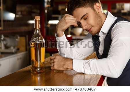 No company needed. Shot of a young handsome guy enjoying a quiet evening at the bar having whiskey smiling with his eyes closed