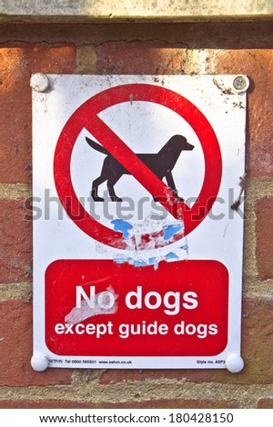 No dogs sign on a brick wall, allowing guide dogs only - stock photo