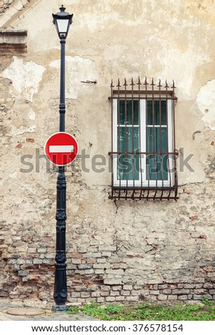 No entry roadsign hanging on street lamp post against background of old weathered house  - stock photo