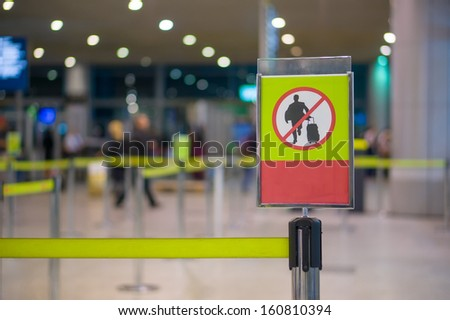 No entry sign - Man with luggage on waiting line at check in desk in airport - stock photo