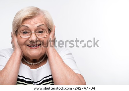 No evil. Pretty elderly woman covering her ears with hands and gesturing three wise monkeys while standing over white background - stock photo
