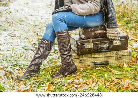 no face person travel Stylish slim woman wait for something on three retro old fashion suitcases Copy space for inscription Girl sit on leather case on grass autumn leaves and snowflakes background