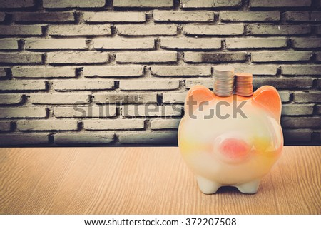 no face piggy bank on perspective floor with old dirty brick wall - stock photo