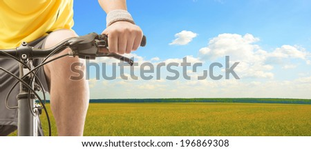 No face Unrecognizable person Biker man at the sunset on thewheat field Legs and hands holding bicycle on sun set sky background