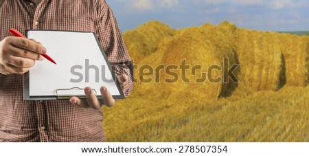 No face Unrecognizable person Businessman hold empty list of paper red pen Business man wear brown shirt Copy space for inscription Experienced agronomist exam wheat hay roll in field Take reading - stock photo