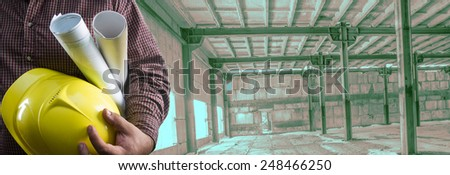 No face Unrecognizable person construction worker man hold in hand blueprint yellow helmet on empty old building inside concrete warehouse background Copy Space for inscription Idea concept safety   - stock photo