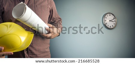 No face Unrecognizable person construction worker man holding in hands  blueprint and yellow helmet on gray texture wall with clock background Empty copy space for inscription - stock photo