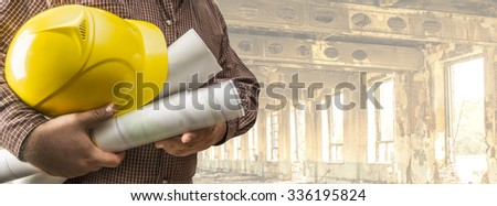 No face Unrecognizable person construction worker man or engineer hold in hand blueprint helmet on empty old building, house inside warehouse background. Space for inscription Idea concept of safety - stock photo