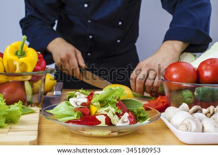 No face. unrecognizable person. cook wear black uniform and cooking vegetables at kitchen on wooden table. focus on vegetarian food. man hold in hand knife