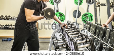 No face Unrecognizable person dumbbells in health club on metal shelf with young adult man lifting weights in mirror reflection on yellow wall texture background Empty space for inscription - stock photo