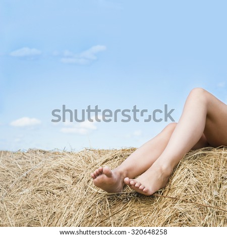 No face. Unrecognizable person. Sunny Summer day. Stack of straw and young slim legs against blue sky with clouds. Idea of healthy feet, freedom, light, rest, relax. Empty space for text