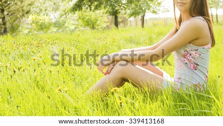 No face. Unrecognizable woman wearing short dress. Summer meadow Girl's barefoot legs sit on fresh spring green grass. Copy space for inscription or objects. Summer yellow flowers near long slim legs