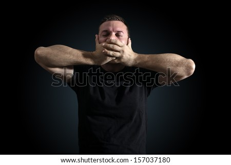 No free speech symbolized by man shutting his mouth with his hands - stock photo