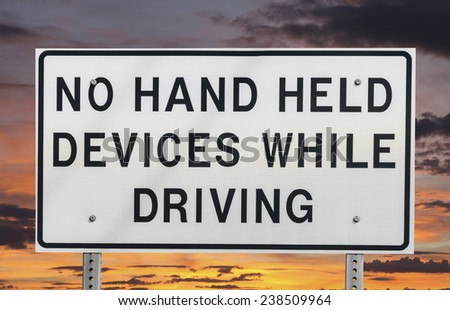 No hand held devices while driving sign isolated with sunset sky. - stock photo